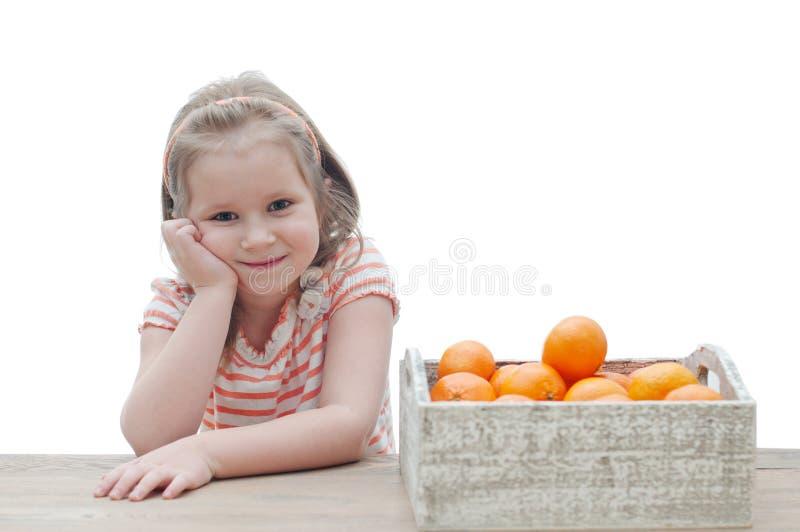 Lächelndes Mädchen mit einem Kasten Mandarinen über weißem Hintergrund lizenzfreies stockfoto