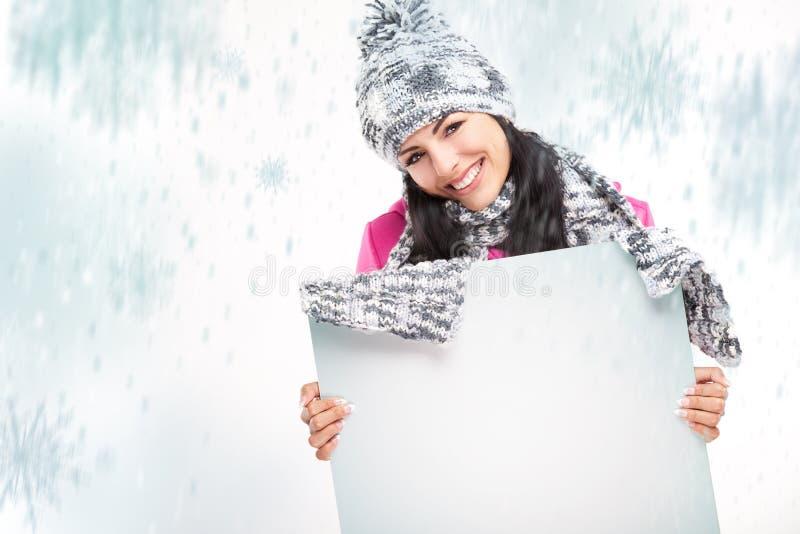 Lächelndes Mädchen mit einem leeren Brett und um das Schneien lizenzfreie stockfotos