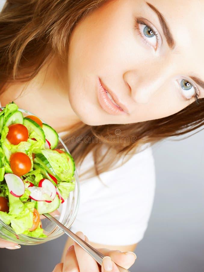 Lächelndes Mädchen mit einem Salat auf einem weißen Hintergrund lizenzfreie stockbilder