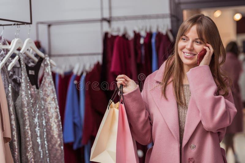Lächelndes Mädchen mit Einkaufstaschen im Shop lizenzfreie stockfotos