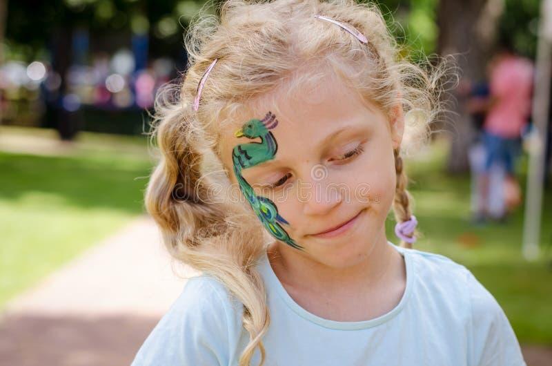 Lächelndes Mädchen mit Gesichtsmalerei des Pfaus lizenzfreie stockbilder