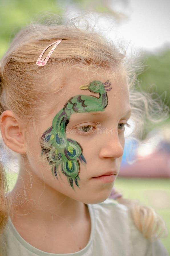 Lächelndes Mädchen mit Gesichtsmalerei des Pfaus stockfotografie