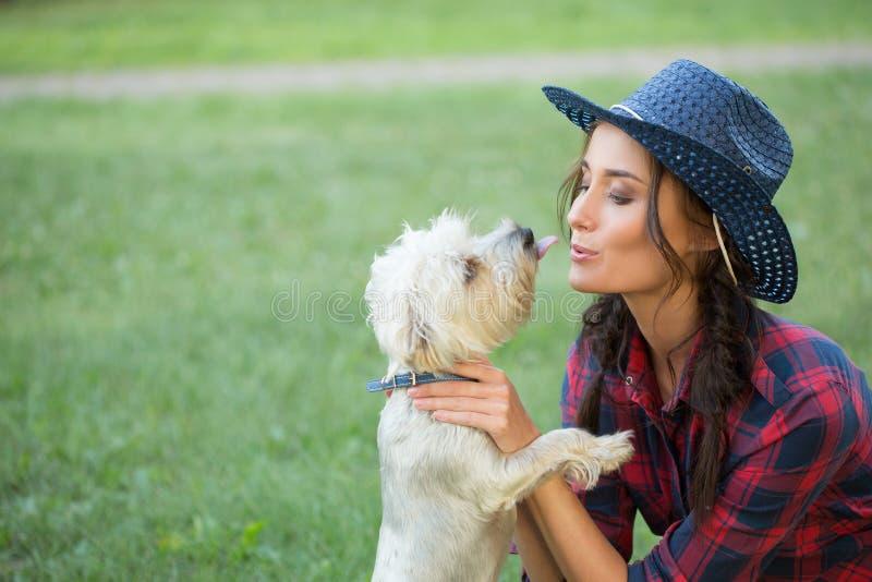 Lächelndes Mädchen mit ihrem kleinen Hund Cowboyhut und stockfotografie