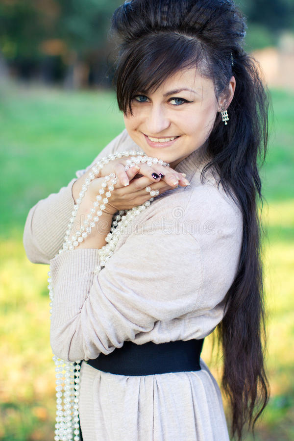 Lächelndes Mädchen mit Perlen in den Händen lizenzfreie stockfotos