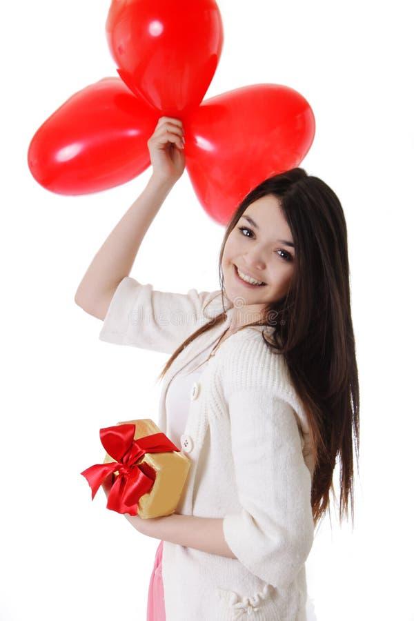 Lächelndes Mädchen mit roten Ballonen und Geschenk stockfoto