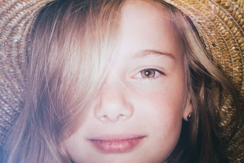 Lächelndes Mädchen mit Strohhut stockfoto