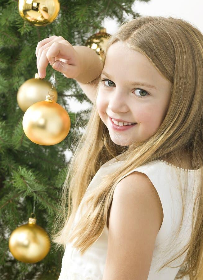 Lächelndes Mädchen mit Weihnachtskugeln nahe bei grünem tr stockbild