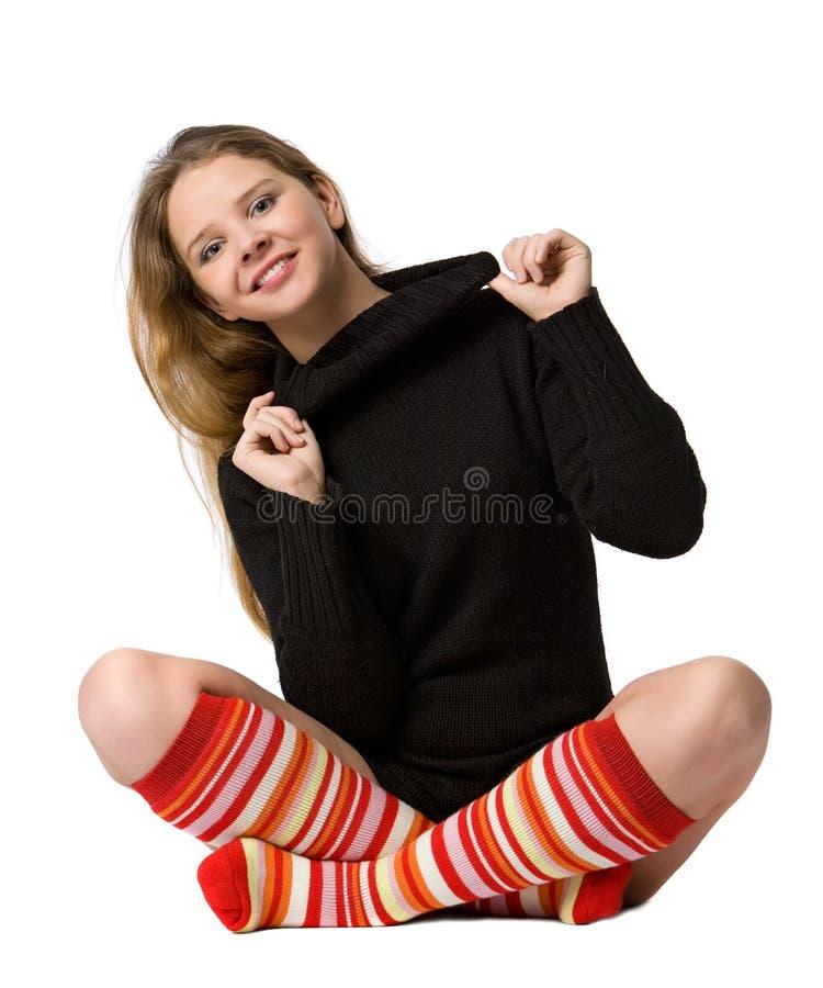 Lächelndes Mädchen sitzt auf dem Fußboden lizenzfreies stockfoto