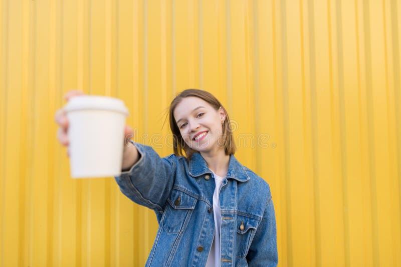 lächelndes Mädchen steht auf einem gelben Hintergrund und bietet einen Papiertasse kaffee an lizenzfreie stockfotos