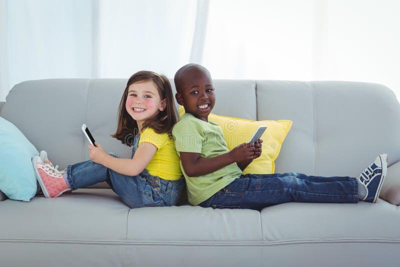 Lächelndes Mädchen und Junge, der Handys verwendet stockfotografie