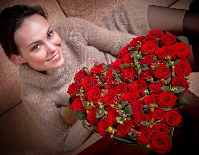 Lächelndes Mädchen und rote Rosen lizenzfreie stockfotos