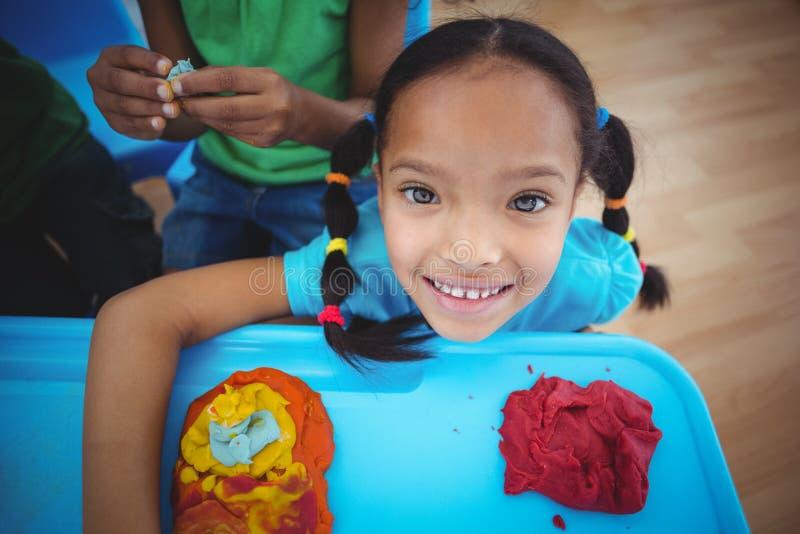 Lächelndes Mädchen, welches die Kamera betrachtet stockfotos