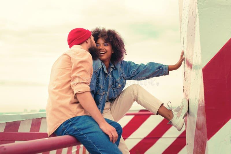 Lächelndes Mädchen, welches die Wand beim Lieben des Mannes küsst ihr Küken berührt stockfotos