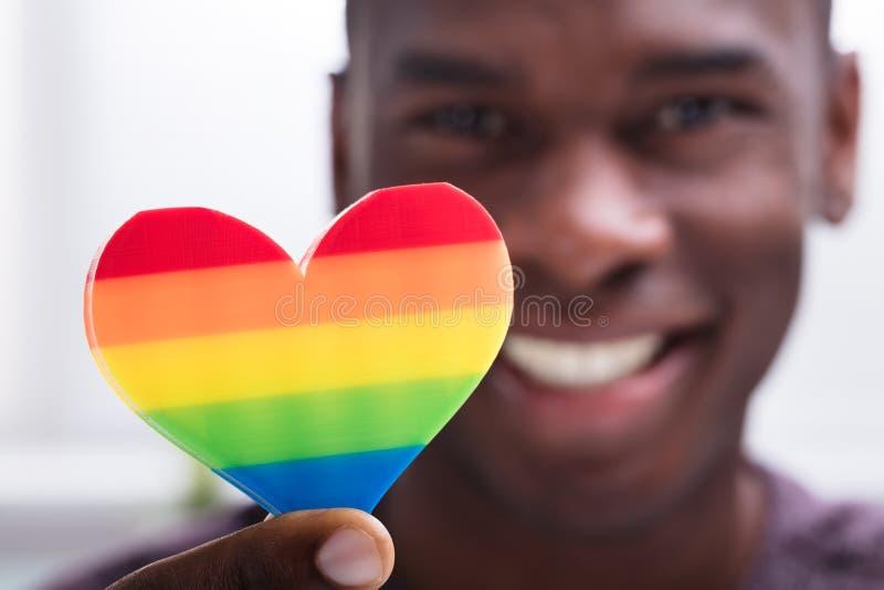 Lächelndes Mann-Holding-Regenbogen-Herz in seiner Hand lizenzfreies stockfoto