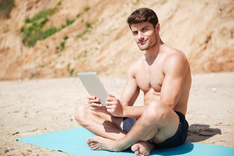Lächelndes Mannsitzen und -anwendung der Tablette auf dem Strand lizenzfreies stockfoto