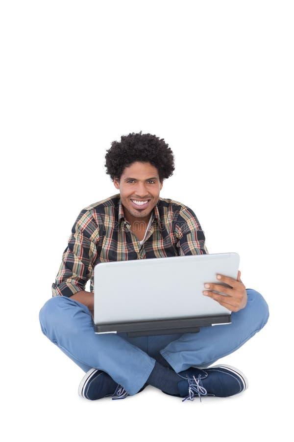 Lächelndes Mannsitzen und -anwendung des Laptops stockfotos