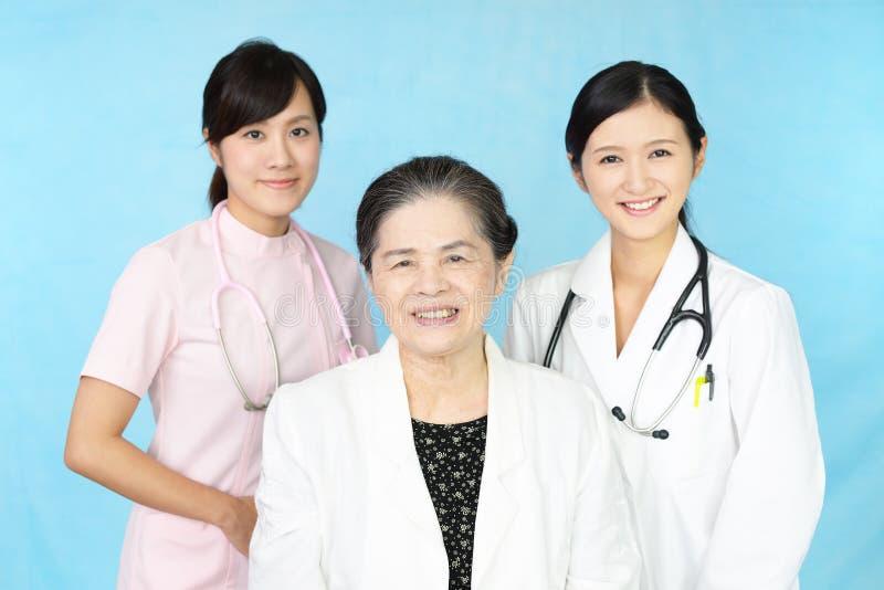 Lächelndes medizinisches Material und eine alte Dame stockbild