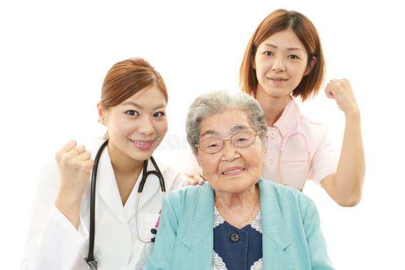Lächelndes medizinisches Personal mit alter Frau stockfotografie