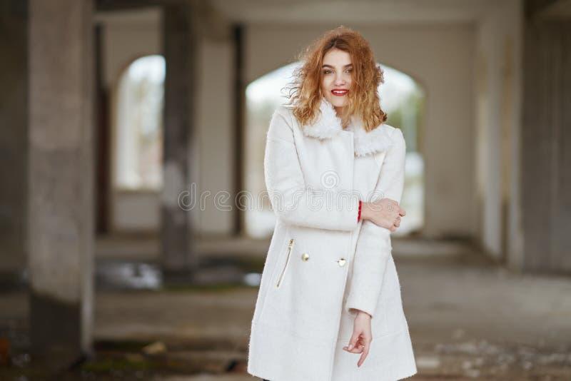 Lächelndes modernes rothaariges Mädchen mit dem Fliegenhaar in einem weißen Mantel, der in einem großen Raum aufwirft lizenzfreies stockbild