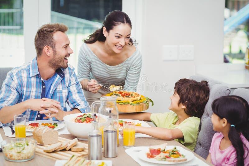 Lächelndes Mutterumhüllungslebensmittel zu den Kindern stockfoto