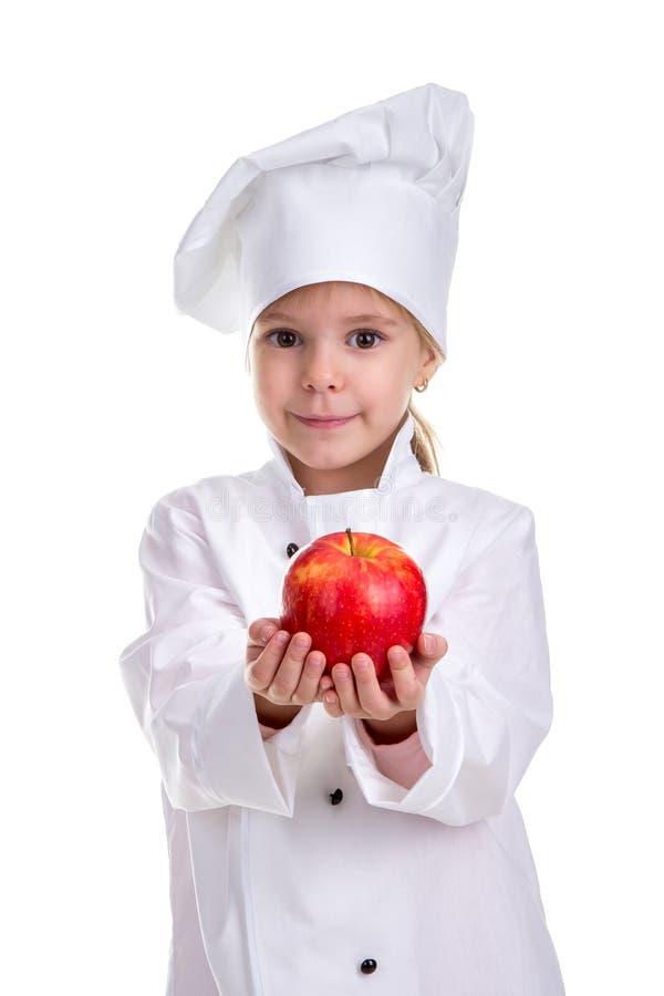 Lächelndes nettes Chefmädchen in einer Kappenkochuniform, den roten Apfel gebend und dehnen die Arme aus Menschliche Gefühle, im  stockfoto