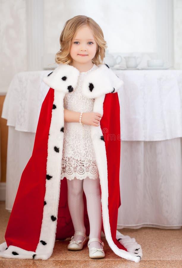 Lächelndes nettes kleines Mädchen, das im königlichen Umhang aufwirft stockbild
