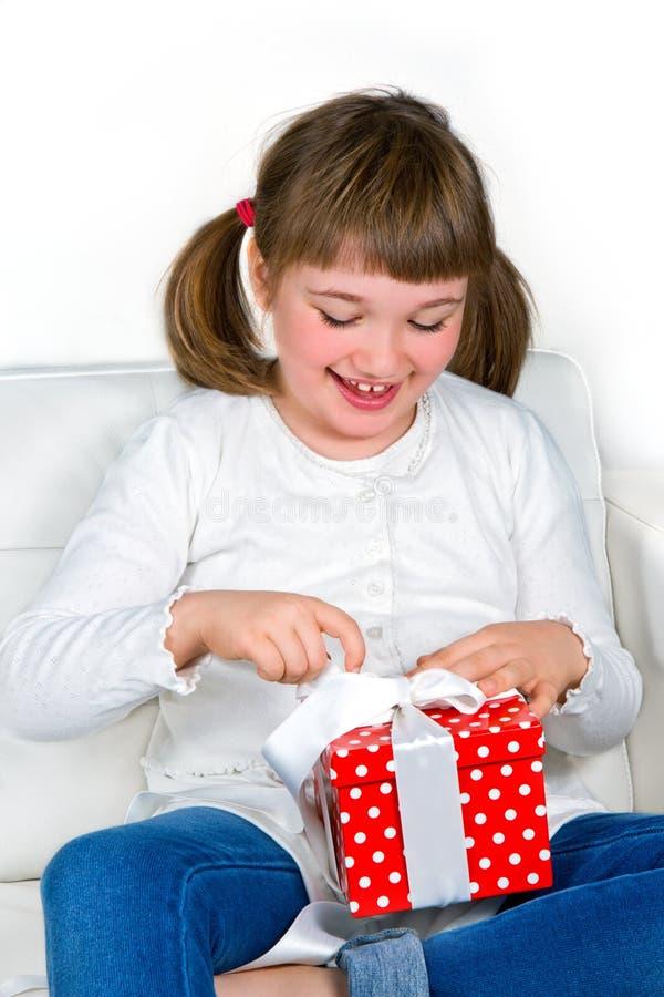 Lächelndes nettes Mädchen, das einen Geschenkkasten öffnet stockfoto