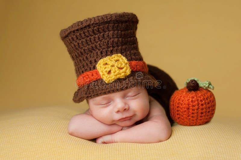 Lächelndes neugeborenes Baby, das einen Pilger-Hut trägt