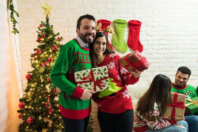 Lächelndes Paar mit Geschenken gegen Freunde zu Hause lizenzfreie stockbilder