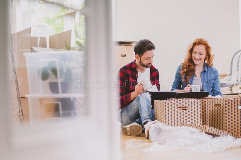 Lächelndes Paare aufpassendes photobook nach Verlegung zu eben gekauftem Haus stockbilder