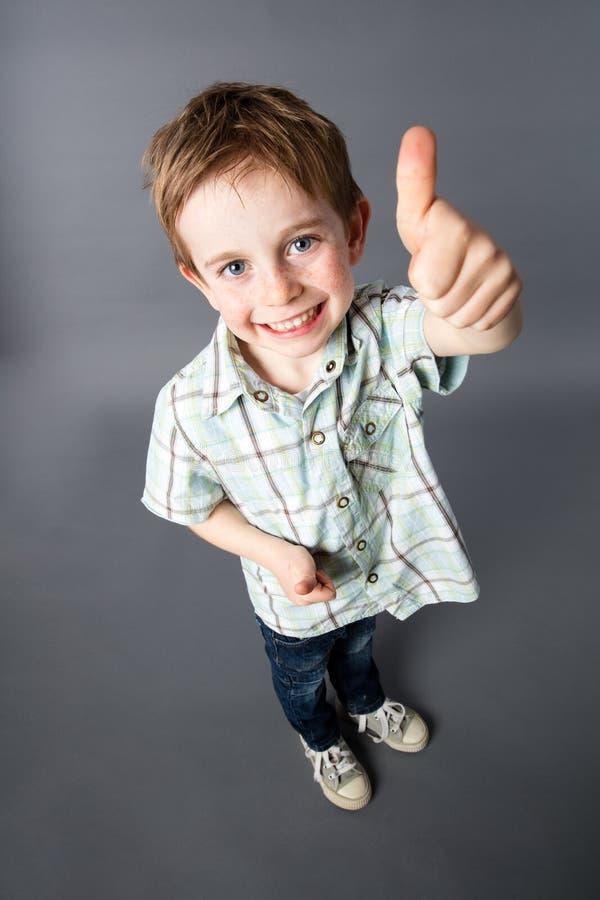 Lächelndes redhair Kind, das O.K. mit den Daumen oben im Vordergrund sagt lizenzfreie stockfotografie