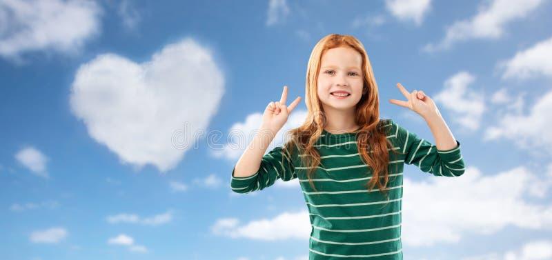 Lächelndes rotes behaartes Mädchen, das Frieden über Himmel zeigt stockbilder