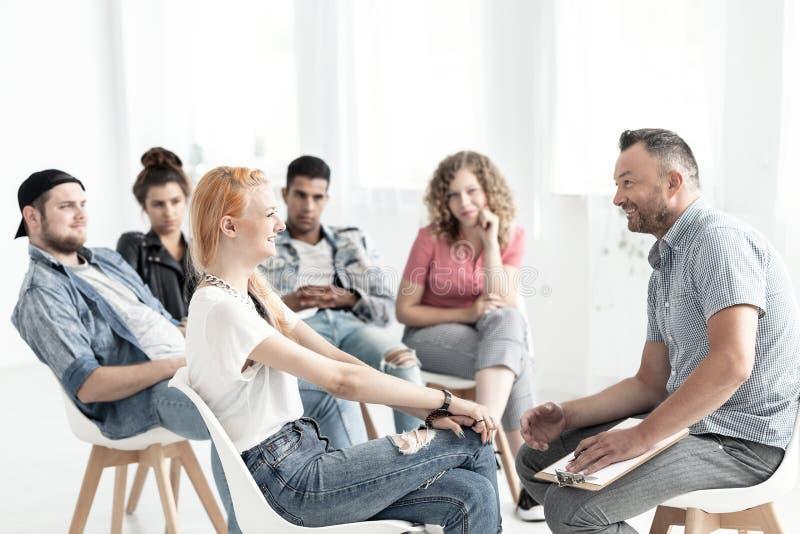 Lächelndes rothaariges Mädchen, das mit einem Therapeuten während des Treffens von FO spricht lizenzfreies stockbild