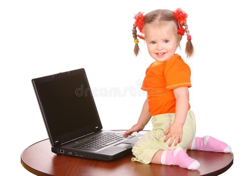 Lächelndes Schätzchen mit Laptop auf Tabelle. lizenzfreies stockbild
