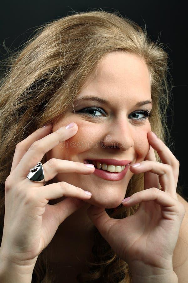 Lächelndes schönes junges Mädchen, das ihren Gesichtsesprit berührt stockbilder