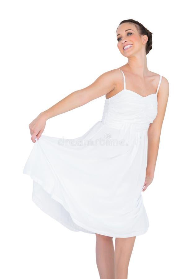 Lächelndes schönes junges Modell im weißen Kleidertanzen lizenzfreies stockbild