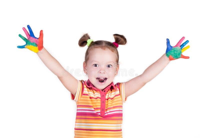 Lächelndes schönes kleines Mädchen mit den Händen in der Farbe stockfotos