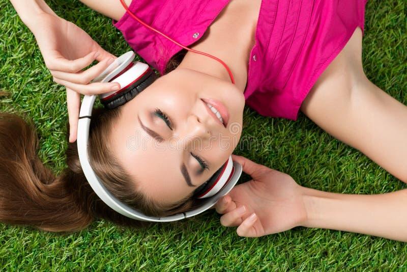 Lächelndes schönes Mädchen der Junge, das auf das Gras in Park listeni legt lizenzfreies stockbild