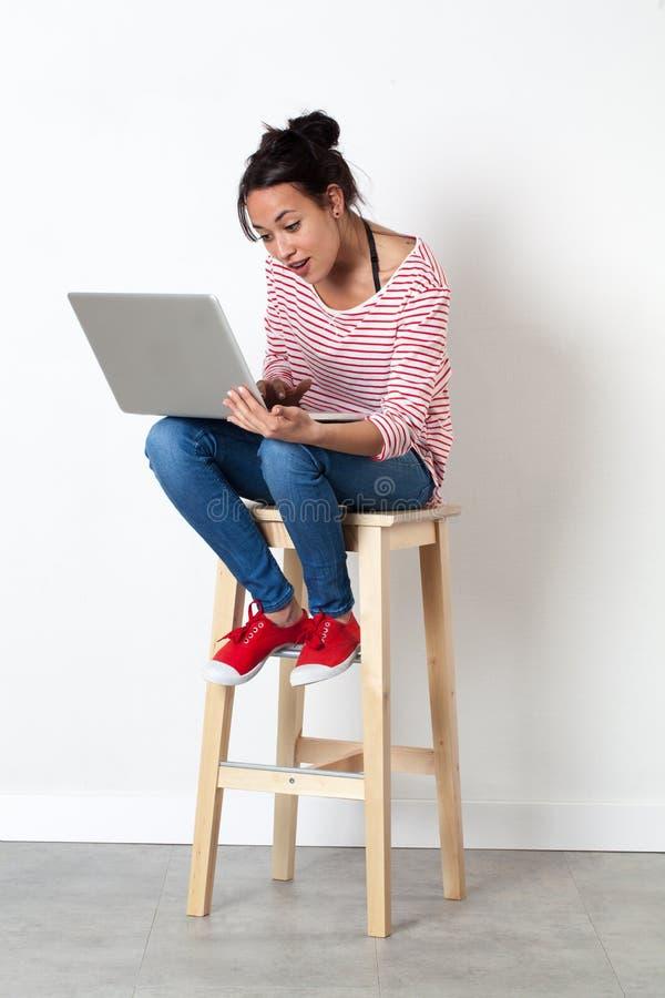 Lächelndes schönes multiethnisches Mädchen, das auf Schemel mit Computer sitzt lizenzfreies stockbild