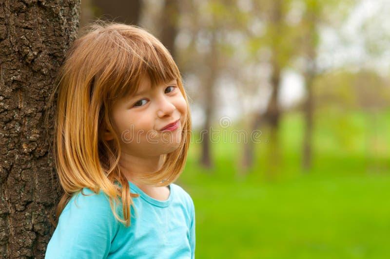 Lächelndes schüchternes kleines Mädchen, das am Baum sich lehnt lizenzfreies stockfoto