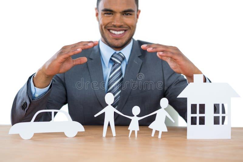 Lächelndes schützendes Papier des Geschäftsmannes schnitt Familie, Haus und Auto mit den Händen heraus stockfotos