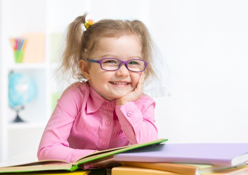 Lächelndes Schauspiel-Lesebuch des Mädchens tragendes lizenzfreies stockfoto