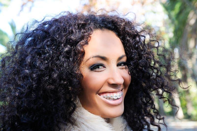 Lächelndes schwarzes Mädchen mit Klammern stockfoto