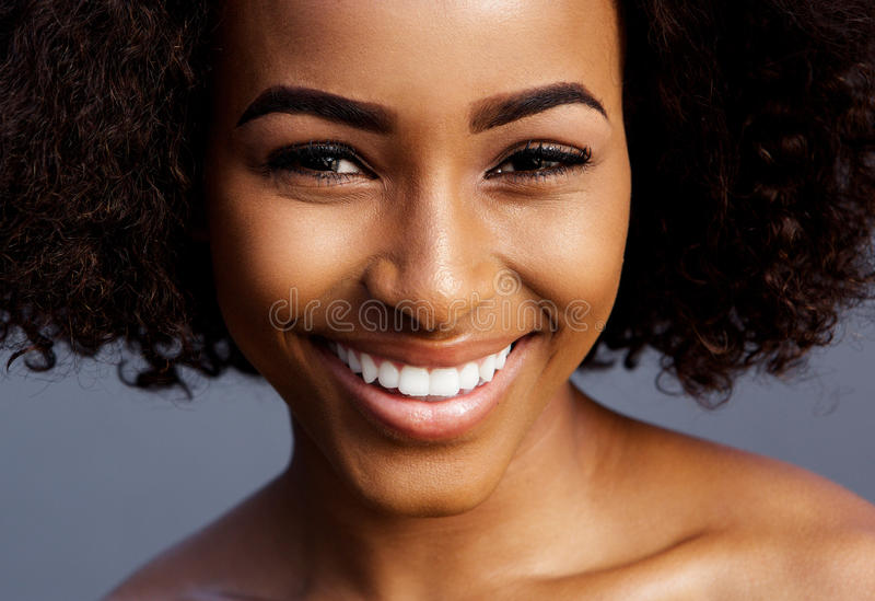 Lächelndes schwarzes weibliches Mode-Modell mit dem gelockten Haar lizenzfreie stockfotografie