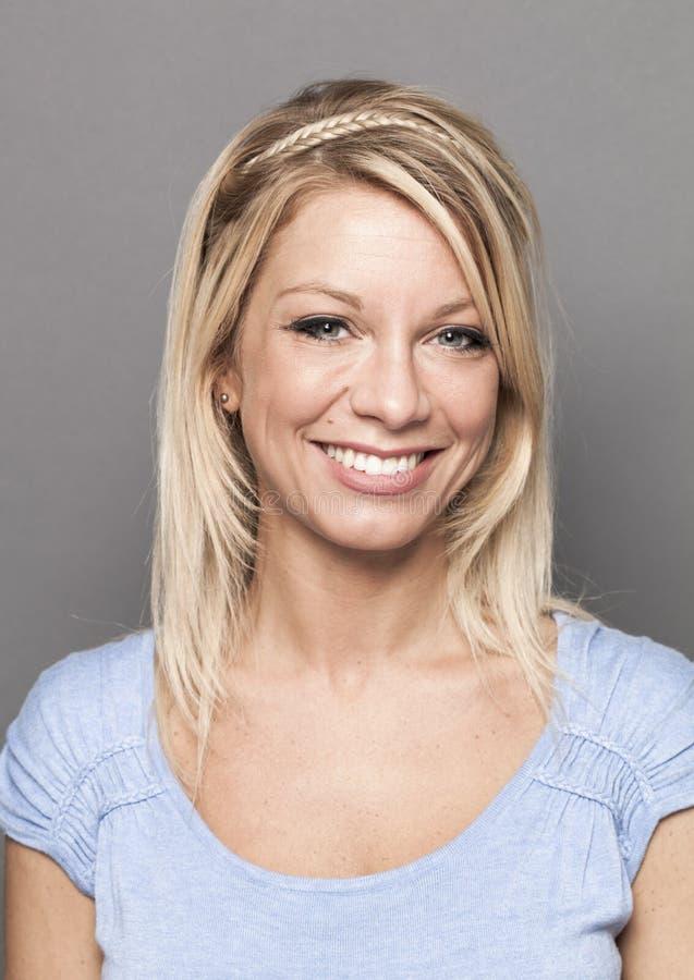 Lächelndes sexy weibliches blondes Mädchen, das hoch entwickeltes Make-up genießt stockfotografie