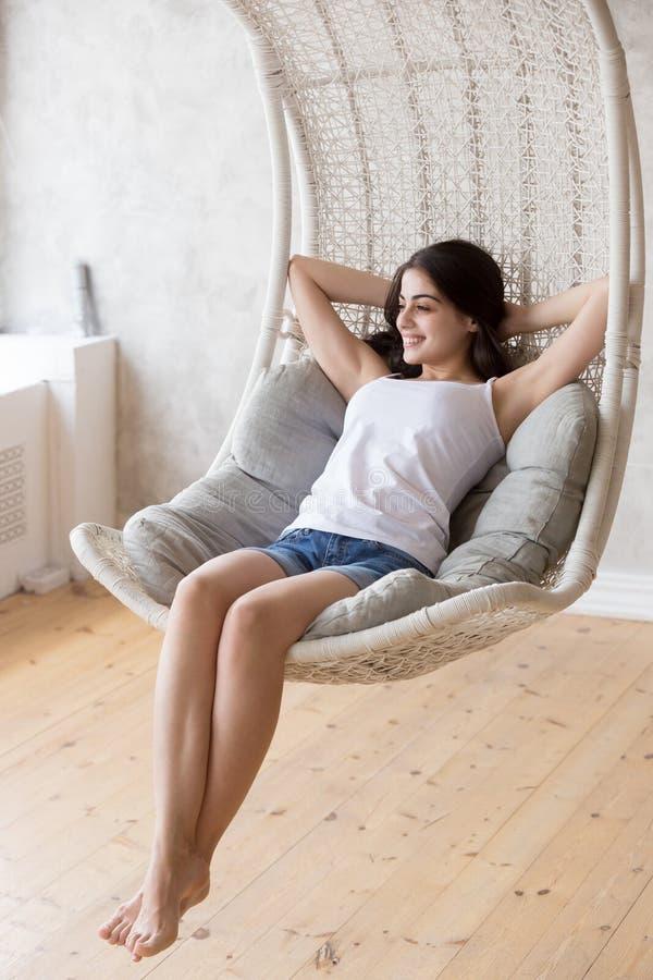 Lächelndes Sitzen der jungen Frau, entspannend in hängendem Stuhl des Aufenthaltsraums lizenzfreie stockfotos