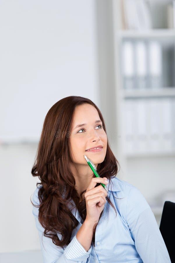 Lächelndes sitzendes Denken der Frau lizenzfreie stockfotos