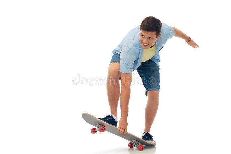 Lächelndes Skateboard des jungen Mannes Reitüber Weiß stockfoto