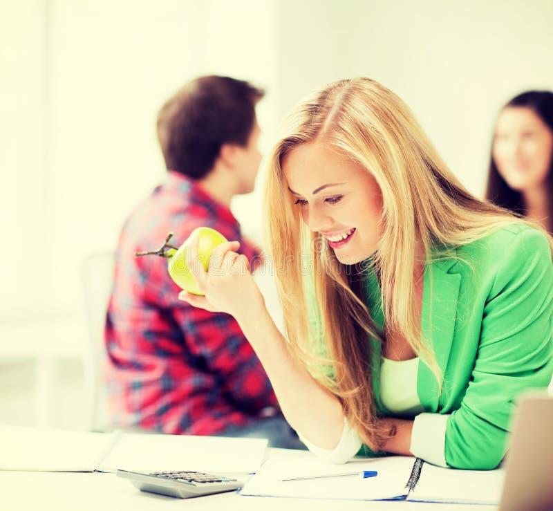 Lächelndes Studentenmädchen, das in der Schule Apfel isst stockfotografie