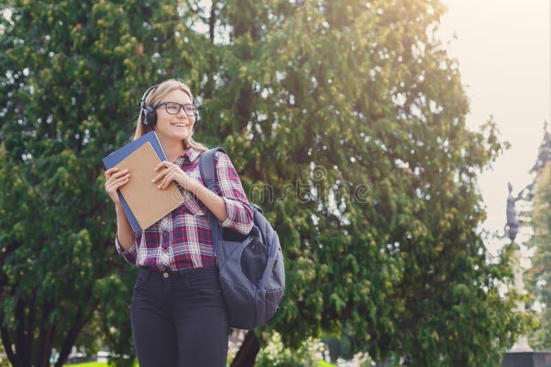 Lächelndes Studentenmädchen mit Büchern im Park draußen stockfotografie